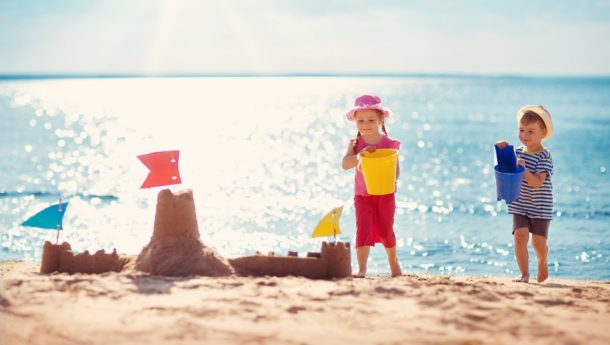 Little boy and girl sandcastle building on the beach