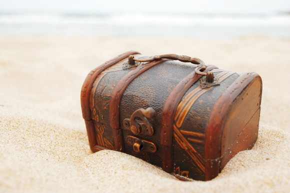 An old treasure chest nestled in the sand on the beach
