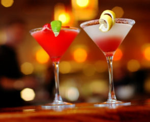 Two red martini-style cocktails accessorised with lemon and lime on a bar top.