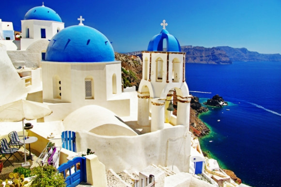 The beautiful Greek blue-domed churches of Caldera and Santorini's breathtaking volcanic backdrop.