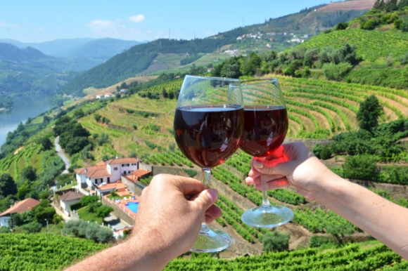 Wine glasses pushed together overlooking the striking Douro Valley in Portugal