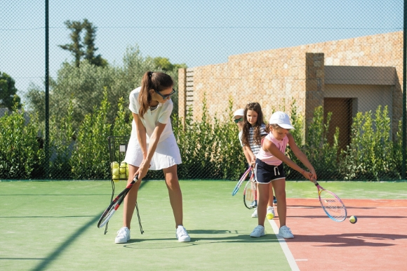 Woman playing tennis with her kids at the brand new Ikos Andalusia