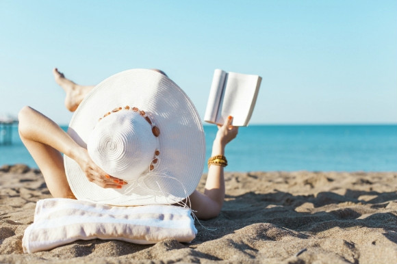 Woman with a big sun hat on reading a book on the beach.