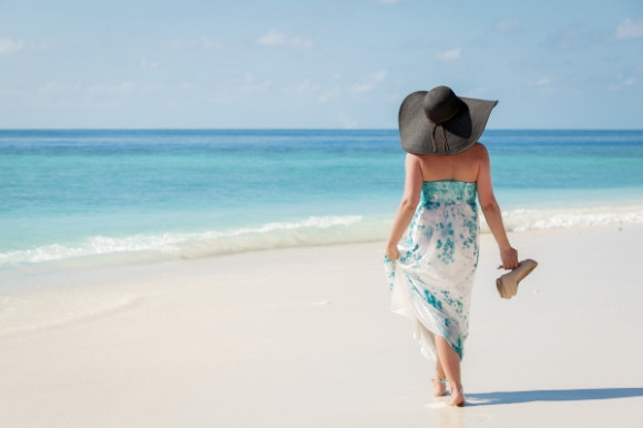 Woman walking barefoot along the white stretch of sand.