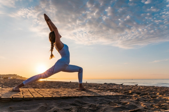 A woman doing yoga on the beach in the morning with the sunrise in the background.