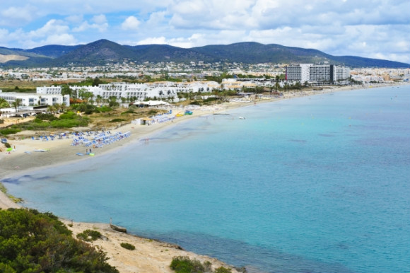 Playa den Bossa beach with views of its epic landscape and nearby hotels.