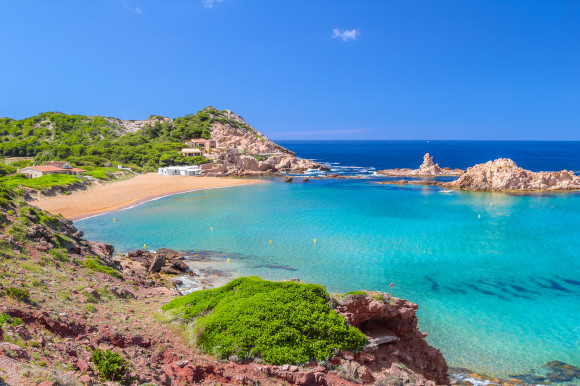 Cala Pregonda Beach on the island of Menorca with shallow blue water and golden sand