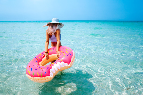 Young woman walking into the shallow sea water holding a doughnut inflatable