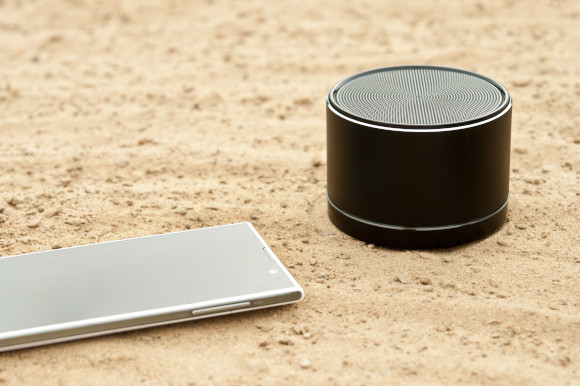 Black Bluetooth speaker on the sand with sliver mobile phone next to it