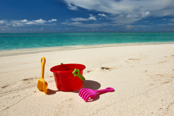 Bucket and spade set placed on a stretch of beach with the ocean and blue skies in the background