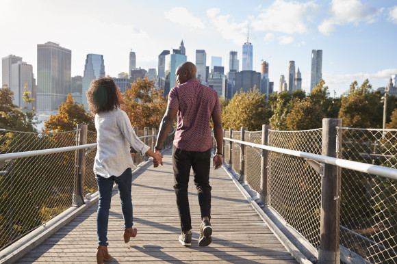 Couple holding hands as they stroll across a bridge with New York City's iconic skyline surrounding them