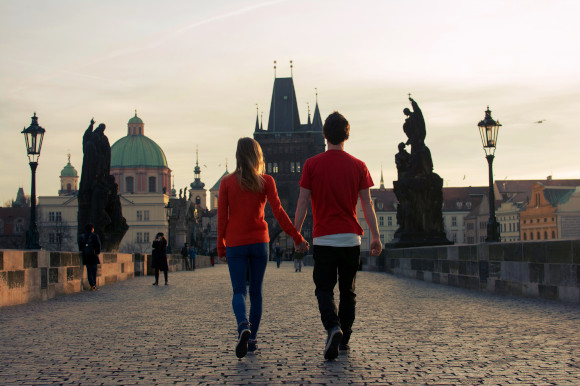 Couple enjoying a romantic stroll over the cobbled Charles Bridge in the city of Prague