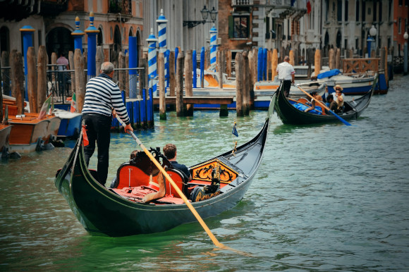 Couple enjoying a romantic gondola ride over the famous waterways of Venice in Italy