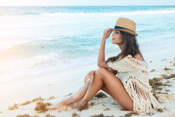 Young woman sitting by the sea wearing a crochet cover-up and straw hat