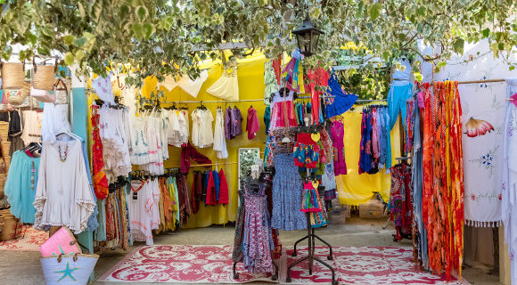 Ibiza's famous hippie markets with stalls selling all kinds of colourful items with shade from the trees above