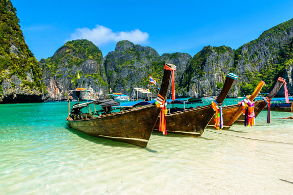 The popular Maya Bay in Thailand with long-tail boats and emerald waters surrounded by tall cliffs