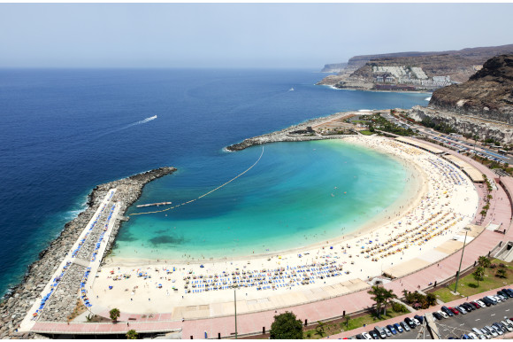 A high up view of the curved, white sand and emerald water at Playa de Amadores Beach in Gran Canaria