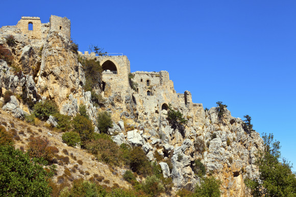 St. Hilarion Castle in Cyprus surrounded by a rocky terrain overgrown with wild bushes