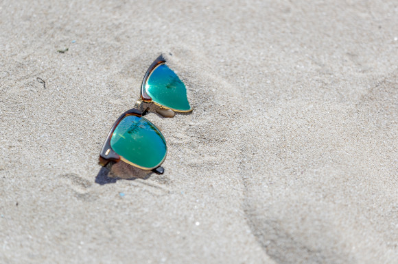 A pair of sunglasses with green lenses placed on the sand