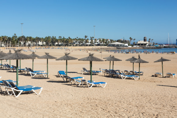 Sun-soaked Caleta de Fuste beach accessorised with sunloungers and straw unbrellas on a sunny day in Fuerteventura