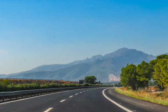 Warm sunny day in Spain and the Road to Madrid surrounded by mountains and lushest greenery