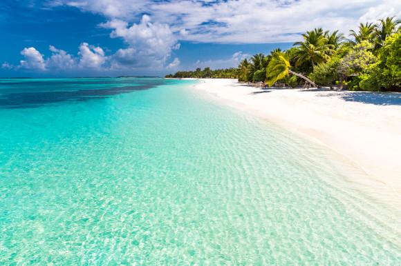 The beautiful Paradise Beach on the Dhigurah Islands in the Maldives with clear waters and a blanket of delicate white sand