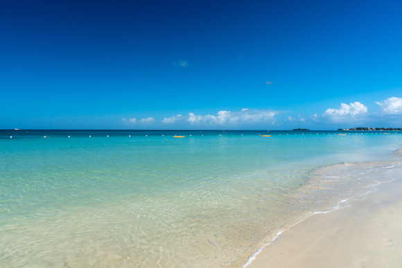 Negril's famouos seven mile beach in Jamaica with beautiful Caribbean waters backed by a bright blue sky