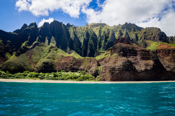 The striking Honopu Beach in Hawaii backed by dramatic volcanic cliffs with shimmering blue waters fronting the sand