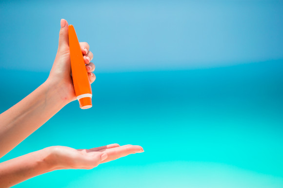 Woman applying sun cream against a bright blue background