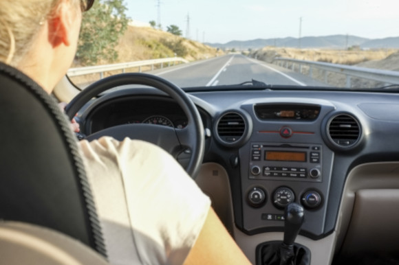 Woman driving on a clear road in Spain alongside the countryside wearing sunglasses on a sunny day.