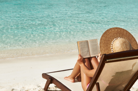 Woman reading a book on a beach sunlounger with white sand and emerald waters in her view