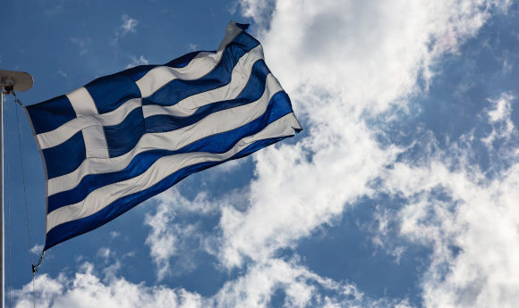 A waving Greek flag positioned against a bright blue sky
