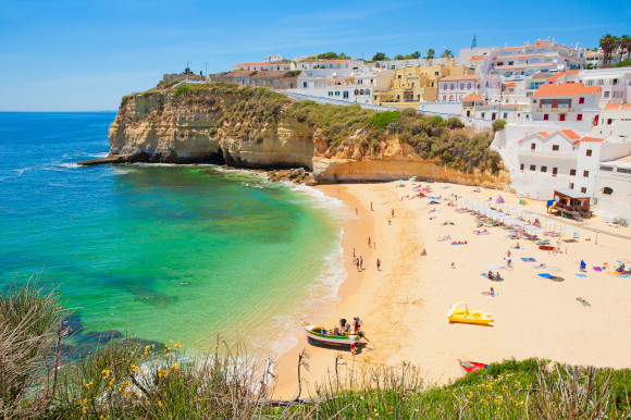 A beautiful beach in Portugal's Algarve with a wide stretch of golden sand and cliffside houses looking over the Atlantic Ocean
