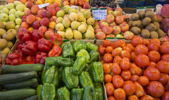 A fruit and vegetable stall in the Algarve region of Portugal containing apples, peppers and cucumbers