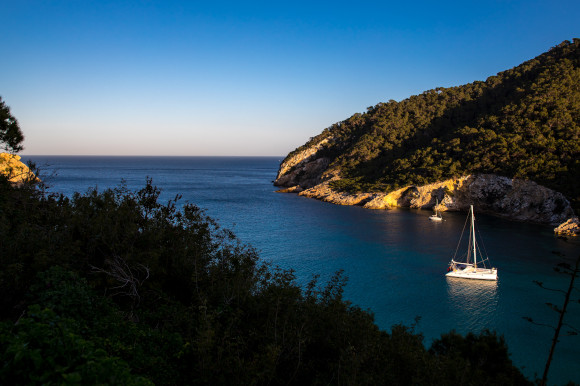 A picturesque beach in Cala Llonga, Ibiza with a boat in the water and green cliffs lit up by the sun