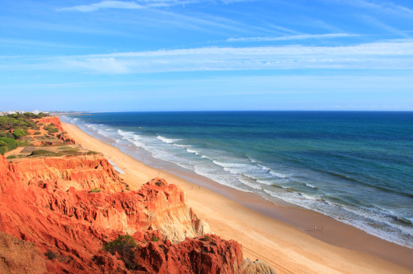 A high up view of the picturesque coastline of Praia da Falésia Beach in Portugal with red cliffs in the background and rippling blue waters