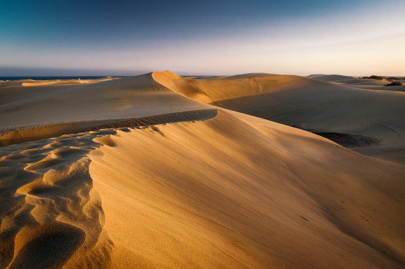 A sunset view showing the sweeping sand dunes of Maspalomas with a glimpse of the sea in the distance on the island of Gran Canaria, Spain