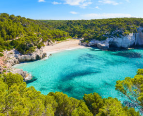 A view of the striking Mitjaneta Beach on the island of Menorca in Spain with shimmering turquoise waters and greenery