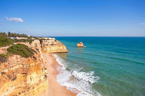 A view of the striking cliffs at Praia da Marinha Beach in Portugal surrounded by golden sand and azure waters