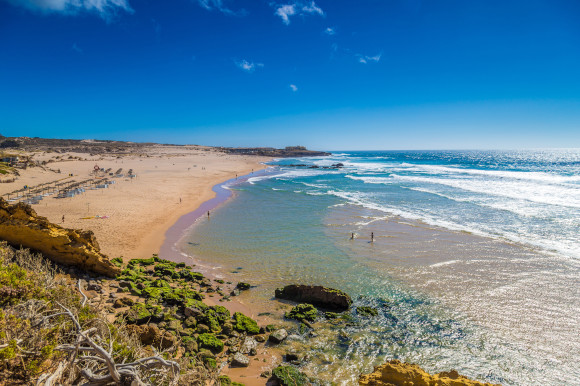 Aerial view of Praia Grande do Guincho Beach in Portugal with shimmering waters and a golden body of sand