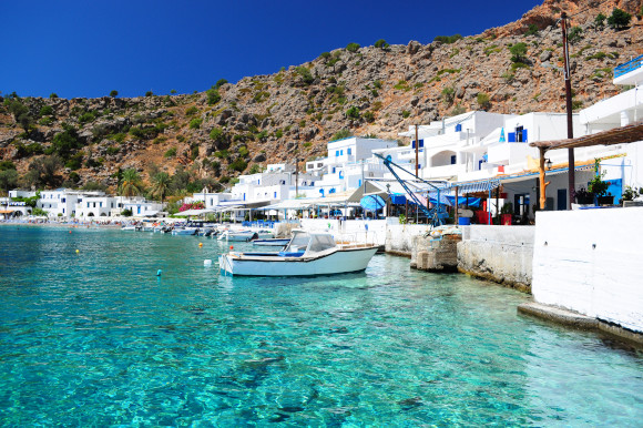 Coastal village in the Greek Island of Crete lined surrounded by traditional whitewashed buildings and beautiful azure waters