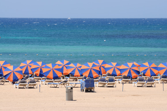 The stunning El Castillo Beach in Fuerteventura filled with umbrellas looking out towards azure waters