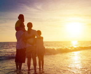 Family huddled together on the beach watching the beautiful sunset over the ocean
