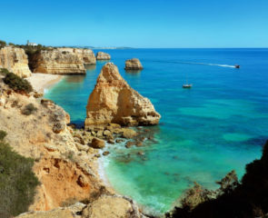 The famous Praia da Marinha Beach in Portugal with limestone cliffs sitting among beautiful, azure waters