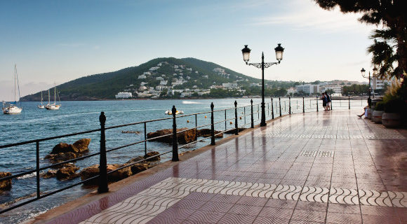 Santa Eulalia's beautiful promenade surrounded by the Mediterranean Sea with a beautiful green hill sitting in the distance