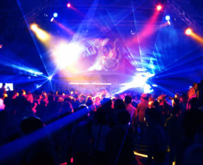 Neon blue, yellow and pink stobe lights flashing at a club with people dancing to the music