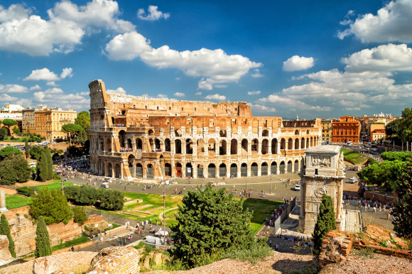 Popular tourist attraction the Colosseum in Rome on a sunny day surrounded by tourists