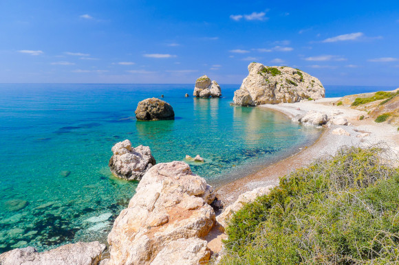 The iconic Rock of Aphrodite under Cyprus'' bright blue sky with azure waters and smaller rocks surrounding it