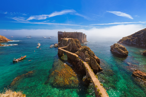 The azure waters and fort of Praia do Carreiro do Mosteiro Beach in Portugal surrounded by boats and rocks