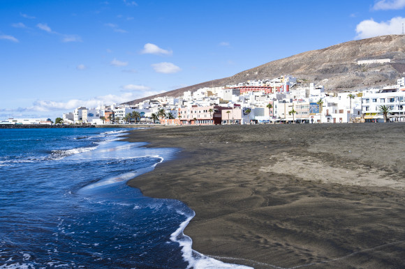 Gran Tarajal Beach in Fuerteventura with its volcanic sands and whitewashed buildings lining the shore